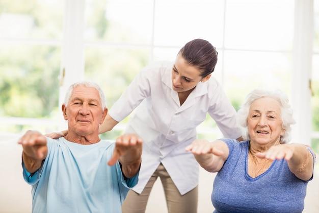 Fisioterapeuta cuidando de pacientes idosos doentes em casa Foto Premium