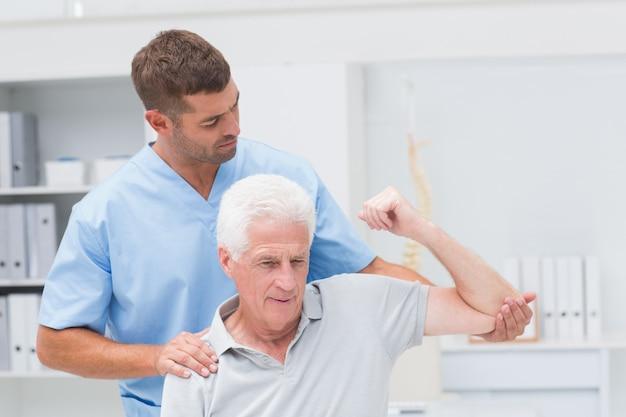 Fisioterapeuta dando fisioterapia ao homem Foto Premium