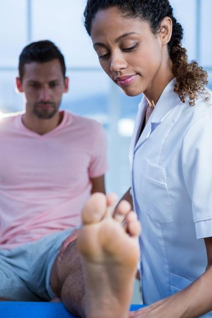Fisioterapeuta dando massagem nas pernas para um homem Foto Premium