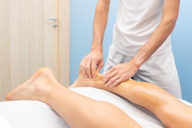 Fisioterapeuta durante tratamento do tendão de aquiles Foto Premium