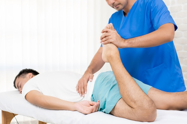 Fisioterapeuta, esticando a perna do paciente do sexo masculino na cama Foto Premium
