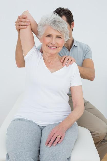 Fisioterapeuta, esticar, um, sorrindo, sênior, womans, braço Foto Premium