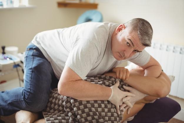 Fisioterapeuta examinando costas de um paciente Foto gratuita