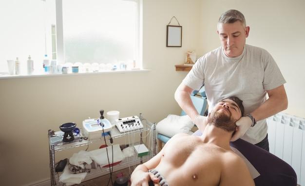 Fisioterapeuta examinando o pescoço de um paciente Foto gratuita