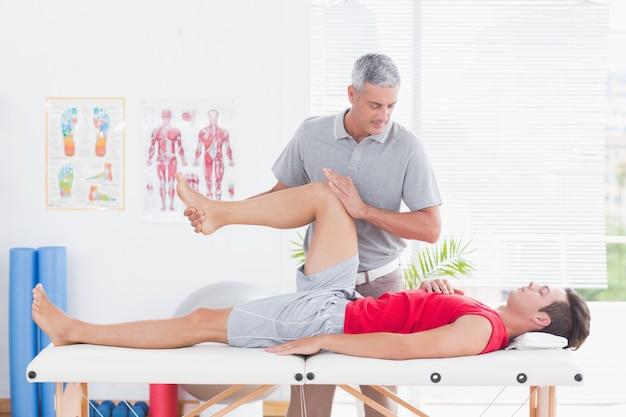 Fisioterapeuta fazendo massagem de perna para seu paciente Foto Premium