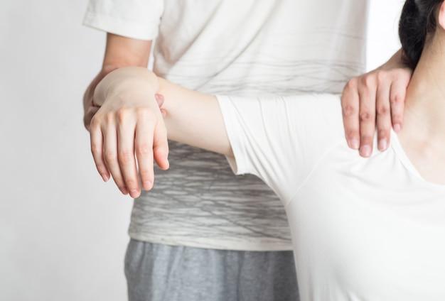Fisioterapeuta feminina profissional, dando massagem nos ombros para homem no hospital Foto Premium