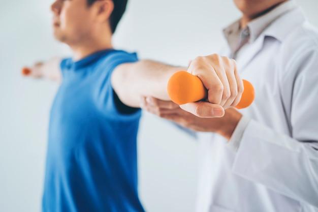 Fisioterapeuta, homem, dar, exercício, com, dumbbell, tratamento, aproximadamente, braço, e, ombro Foto Premium