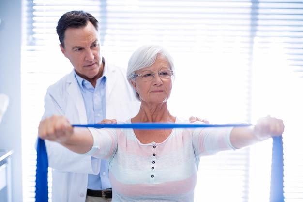 Fisioterapeuta masculino dando massagem nos ombros para mulher sênior Foto Premium