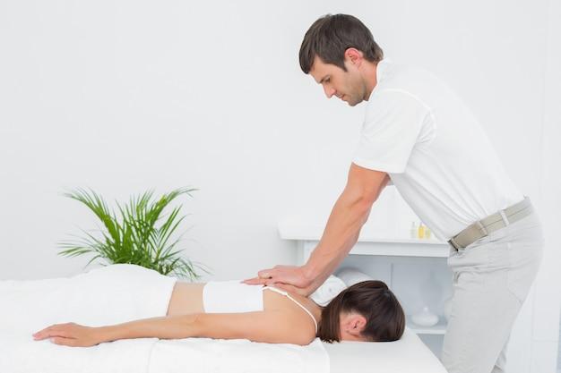 Fisioterapeuta masculino massageando mulher de volta Foto Premium
