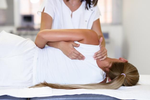 Fisioterapeuta profissional que dá massagem no ombro à mulher loira Foto gratuita