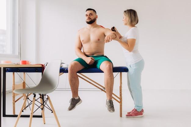 Fisioterapeuta que aplica a fita de kinesio aos pacientes feridos ombro Foto Premium