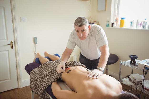 Fisioterapeuta realizando agulhamento eletro-seco no paciente Foto gratuita