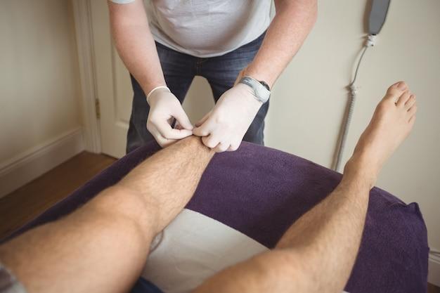 Fisioterapeuta realizando agulhamento seco na perna de um paciente Foto gratuita