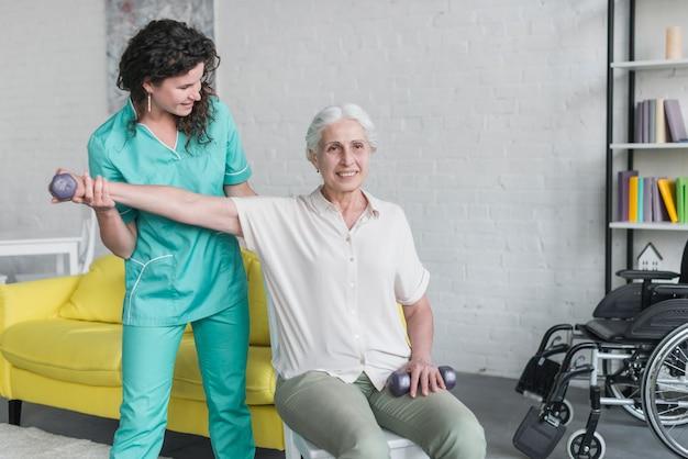 Fisioterapeuta trabalhando com paciente idoso na clínica moderna Foto gratuita