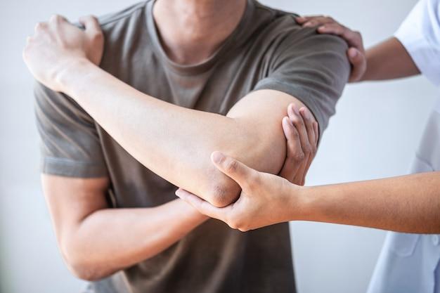 Fisioterapeuta tratando ferimento no braço de paciente atleta do sexo masculino Foto Premium