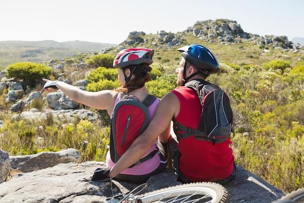 Fit casal ciclista sentado no topo olhando em volta Foto Premium