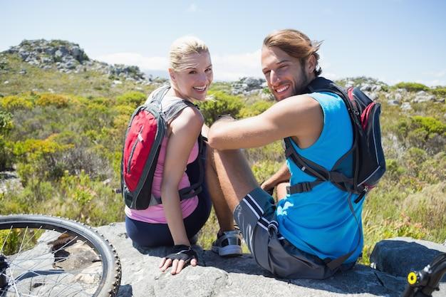 Fit casal de ciclistas fazendo uma pausa no pico rochoso sorrindo para a câmera Foto Premium