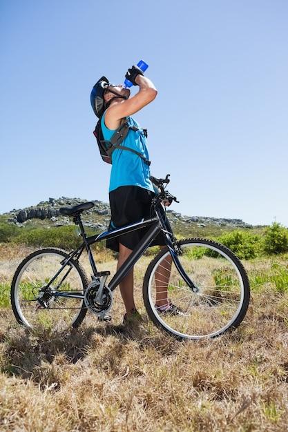 Fit ciclista andando no campo tomando uma bebida Foto Premium
