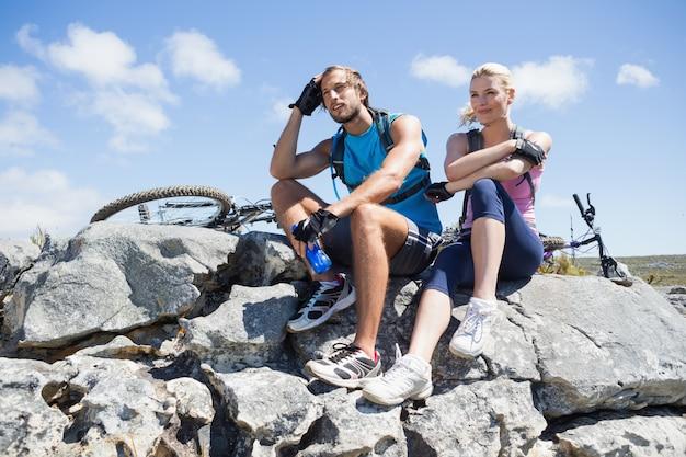 Fit ciclista casal fazendo uma pausa no pico rochoso Foto Premium