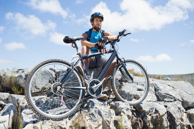 Fit ciclista tomando uma pausa no pico roco Foto Premium