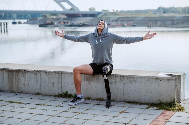 Fit desportista deficiente caucasiano saudável com perna artificial e capuz na cabeça sentado no cais com os braços abertos. Foto Premium
