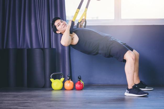 Fit homem fazendo exercício de prancha para espinha traseira por flexões com alças de aptidão de corda no ginásio Foto Premium