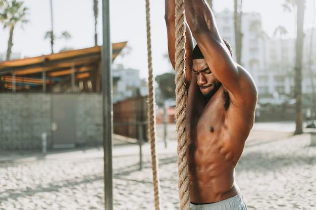 Fit homem malhando com cordas Foto Premium