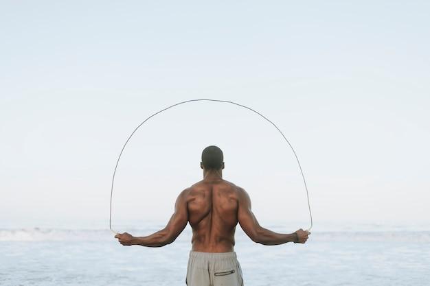 Fit homem pulando corda na praia Foto Premium