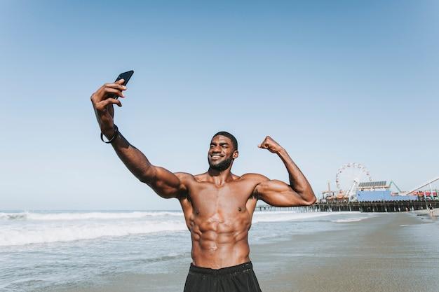 Fit homem tomando uma selfie por santa monica pier Foto gratuita