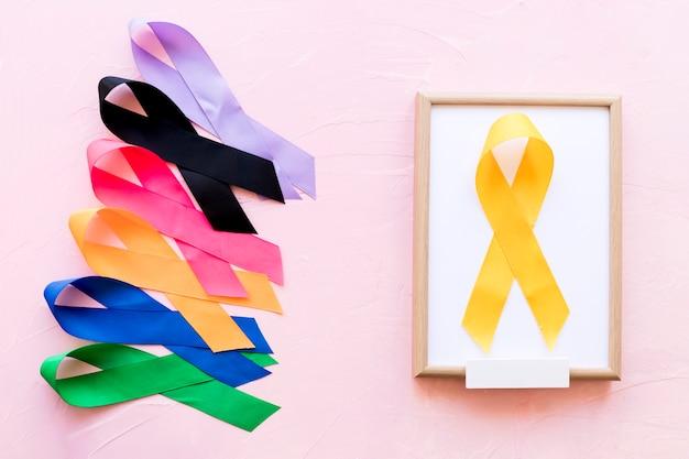 Fita amarela na moldura de madeira branca perto da linha da fita colorida da consciência Foto gratuita