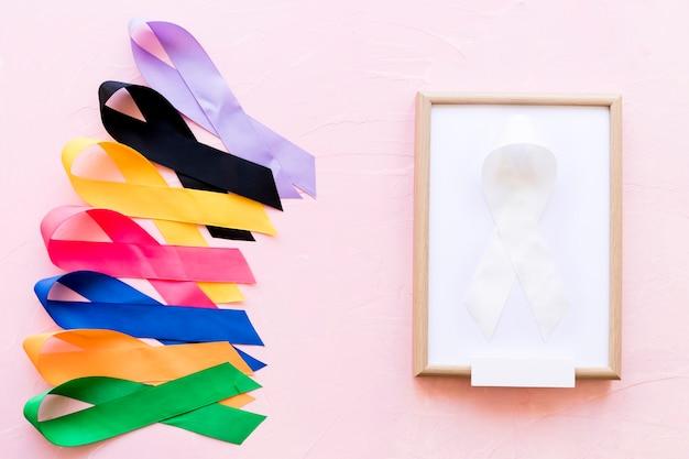 Fita branca em moldura de madeira branca perto da linha da fita colorida da consciência Foto gratuita