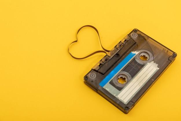 Fita cassete de áudio em fundo amarelo. filme moldando o coração, cartão postal do dia dos namorados. espaço vazio. Foto Premium