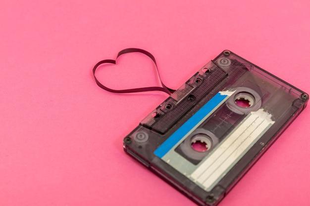 Fita cassete de áudio em fundo rosa. filme moldando o coração, cartão postal do dia dos namorados. espaço vazio. Foto Premium