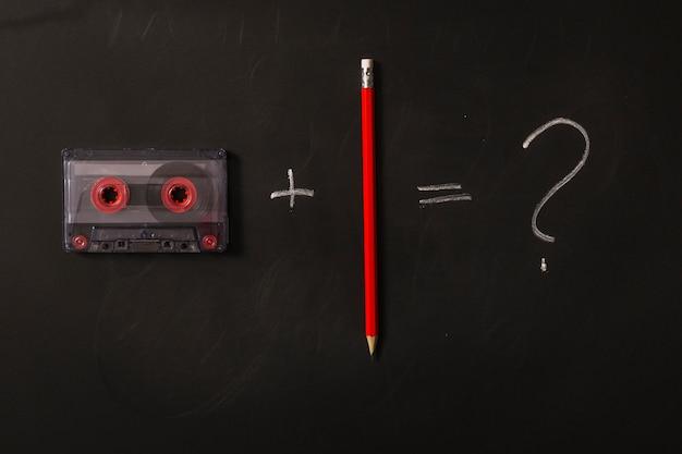 Fita cassete, mais lápis vermelho é igual a ponto de interrogação em fundo preto Foto gratuita