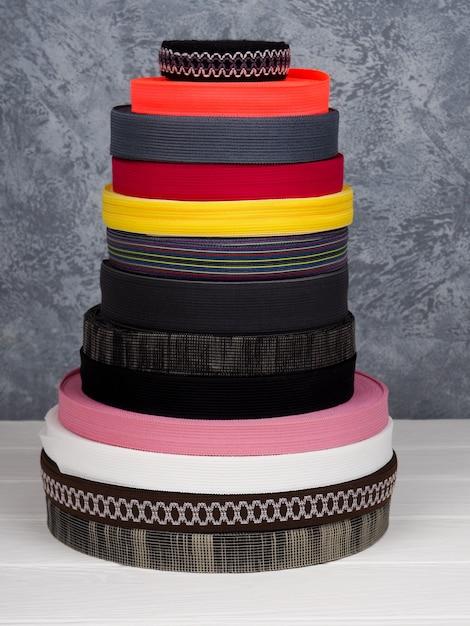 Fita de cores diferentes em bobinas, muitas bobinas multicoloridas para a indústria têxtil, fabricação de roupas Foto Premium