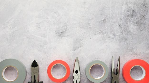 Fita isolante e alicate dispostos em linha em piso de concreto de cimento branco Foto gratuita