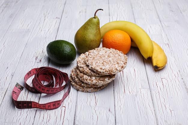 Fita métrica, bolinhos de arroz, avokado, pêra, laranja e banana mentem sobre a mesa de madeira Foto gratuita