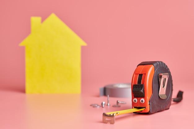 Fita métrica de metal conceito engraçado. renovação da casa. reparo em casa e conceito redecorado. casa amarela em forma de figura Foto Premium
