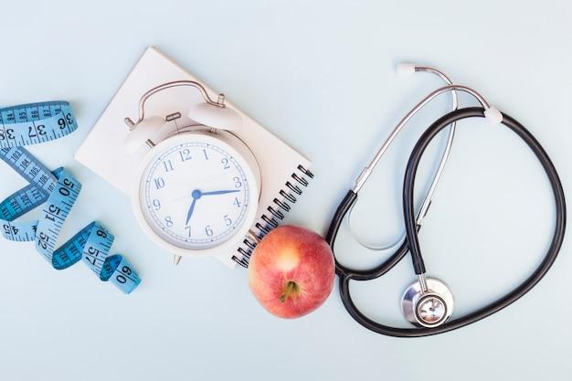 Fita métrica; despertador; bloco de notas em espiral; maçã e estetoscópio no fundo azul Foto gratuita