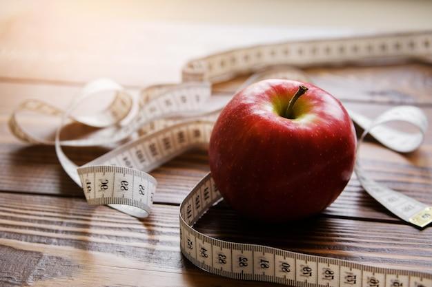 Fita métrica e vermelho maçã no fundo de madeira Foto Premium