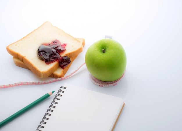 Fita métrica, embrulhado, ao redor, um, maçã verde, com, fatia branco Foto Premium