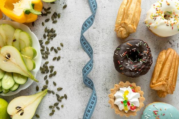Fita métrica entre alimentos saudáveis e insalubres Foto gratuita