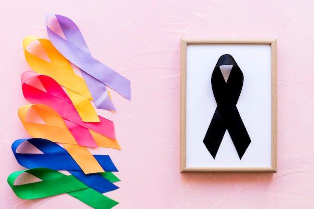 Fita preta na moldura de madeira branca perto da linha da fita colorida da consciência Foto gratuita
