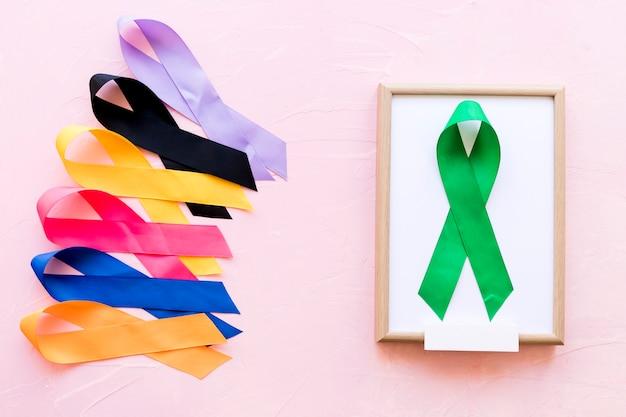 Fita verde na moldura de madeira branca perto da linha da fita colorida da consciência Foto gratuita