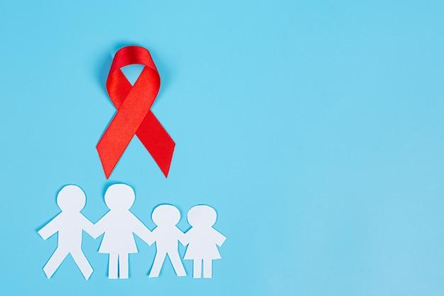 Fita vermelha do conhecimento e papel cortado em família, conscientização sobre o hiv, dia mundial da aids e dia mundial da saúde sexual. Foto gratuita