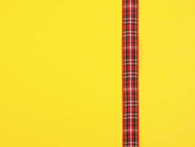 Fita vermelha na caixa em um fundo amarelo Foto Premium