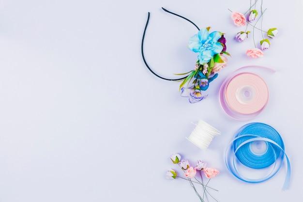 Fitas de cabelo feitas à mão com flores artificiais; carretel e fita em pano de fundo branco Foto gratuita