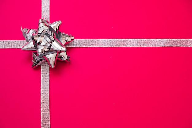 Fitas de prata com curva no fundo vermelho. conceito de presente de natal. vendas Foto Premium