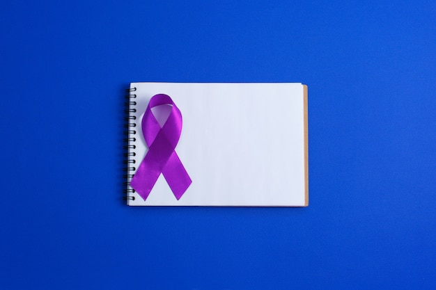 Fitas roxas e caderno aberto, doença de alzheimer, câncer de pâncreas, conscientização sobre epilepsia, conscientização sobre violência doméstica, Foto Premium