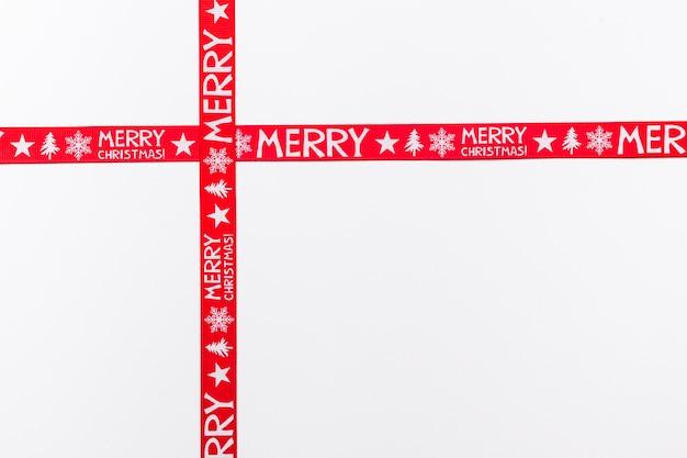 Fitas vermelhas cruzadas dizendo feliz natal Foto gratuita